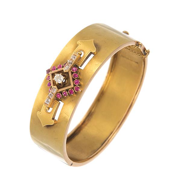 Pulsera en oro amarillo con adorno central de diamantes y rubíes