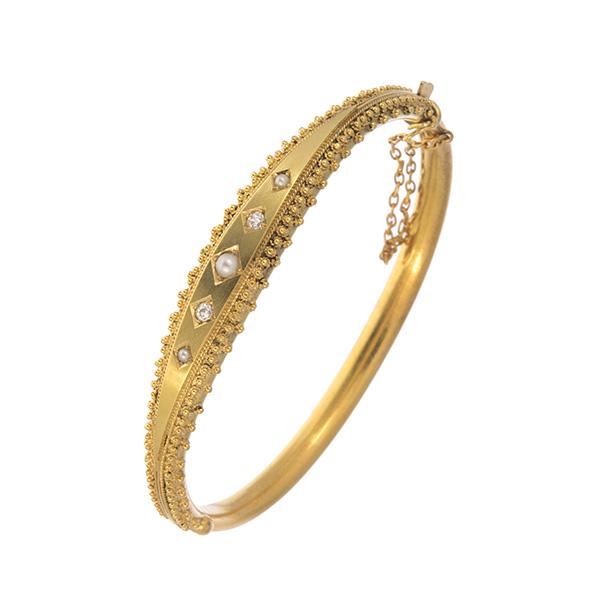 Pulsera rígida de oro con diamantes y perillas.